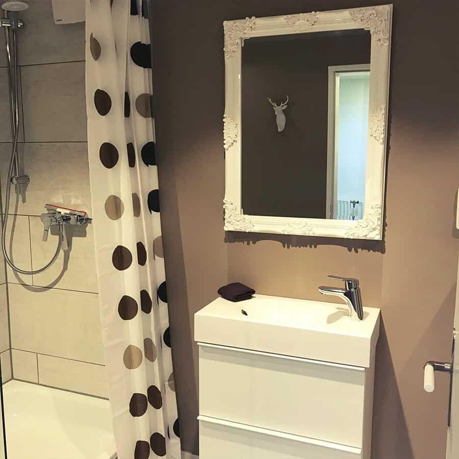 Dusche mit Spiegel und Waschbecken