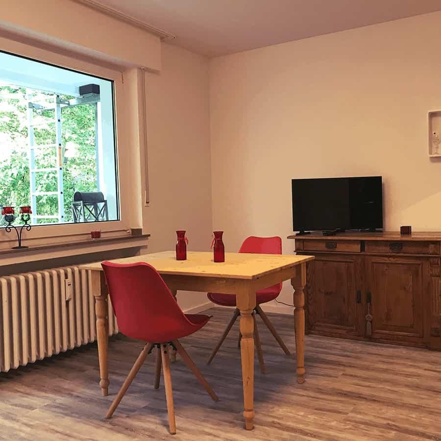 TV mit Kommode, Stühlen und Tisch