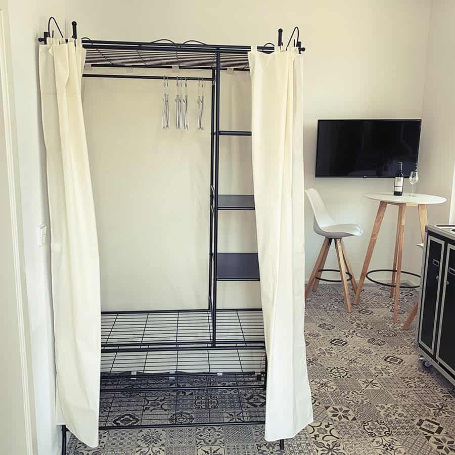 Garderobe mit Vorhang sowie Kleiderbügeln